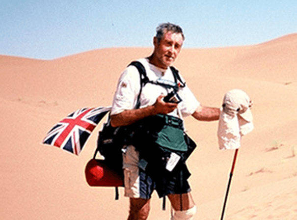 miles hilton barber stood in a desert with an english flag